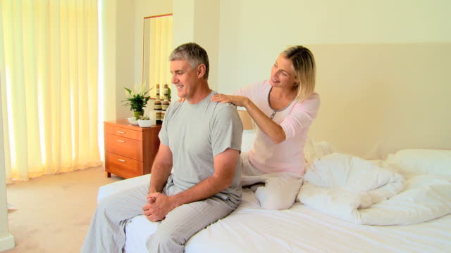Young woman giving her husband a massage in bedroom / Cape Town, Western Cape, South Africa