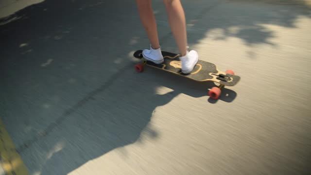 A young woman goes longboard skateboarding.