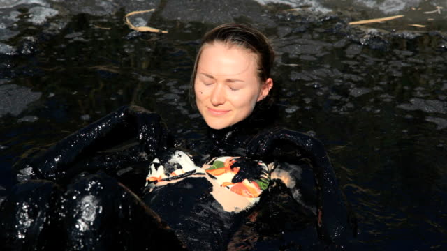 CLIP Young woman have mud therapy outdoors summer