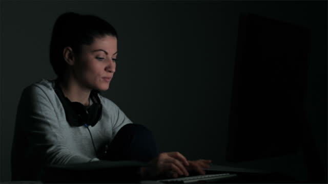 Young woman having a chat in front of the computer late in night.