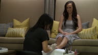 Young woman having her toenails polished