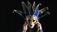 Junge Frau versteckt hinter einer Maske