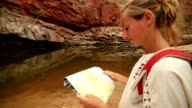 Young woman hiking in the outback reads map for directions