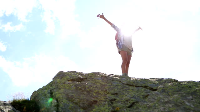 Young woman hiking on mountain peak-Success and freedom