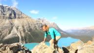 Jonge vrouw wandelen staat op een berg boven armen gestrekt