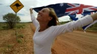 Young woman holding Australian flag in air near Kangaroo sign