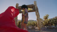 SLO MO. Young woman holds a flowing red scarf that flaps in front of camera in the desert wind.