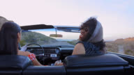 MS. Young woman holds scarf in the air in classic convertible and laughs with friends on desert road trip.
