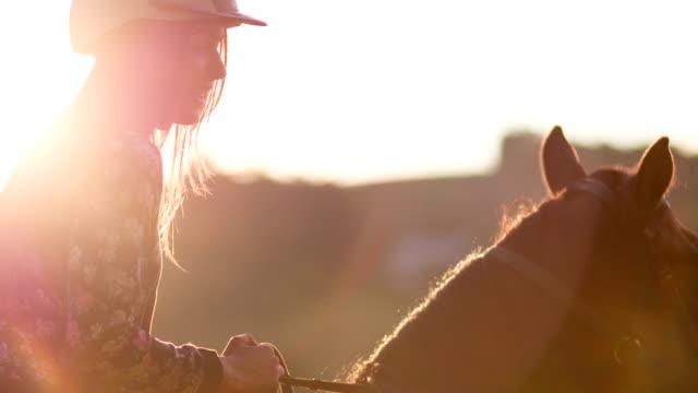 Young woman horseback riding at sunset