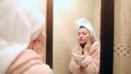 Young woman in bathrobe applying facial moisturizer.
