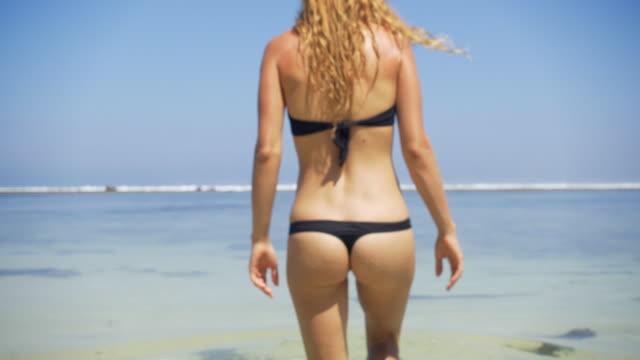 Young woman in bikini walking into the ocean