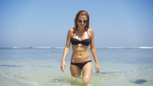 Young woman in bikini walking out of the ocean