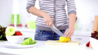 Young woman in kitchen chopping pepper