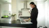 MS Young woman in kitchen holding coffee cup using laptop