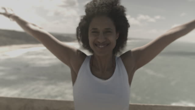 Young woman in Portugal enjoying wind by oceanside, smiling