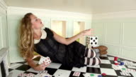 Young woman in small room throwing playing cards