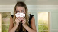Young woman in small room with hand of playing cards