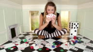 Young woman in small room with playing cards, poker chips and dice