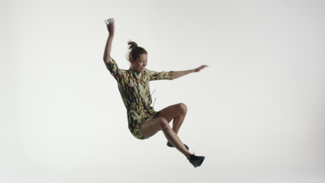 Young woman in smart casual dress jumping on trampoline in studio
