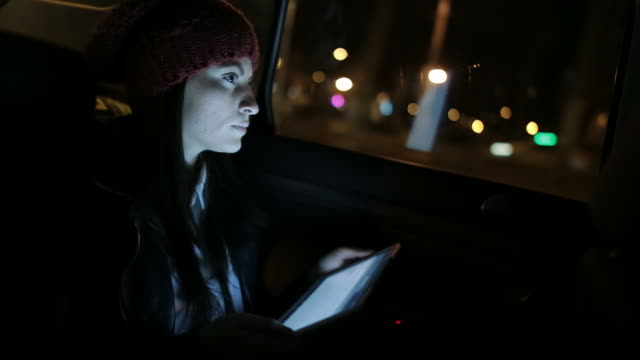 Young woman in the car using the tablet.