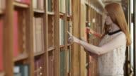 TU DS jonge vrouw in de bibliotheek op zoek naar een boek met behulp van een tablet