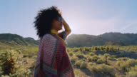 SLO MO. Young woman in vintage dress gazes off in empty desert.