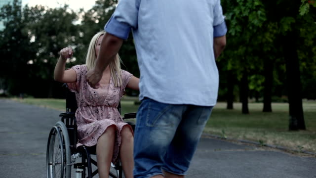 HD: Young Woman in wheelchair at park.