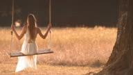 SLO MO TD jonge vrouw in witte jurk swingende onder een grote boom