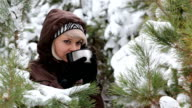 Young woman is drinking tea in the winter forest.