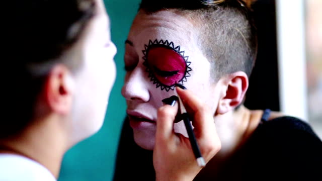 Young Woman Is Getting Sugar Skull Mask Drawn