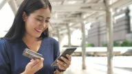 Young Woman is shopping online using a smartphone