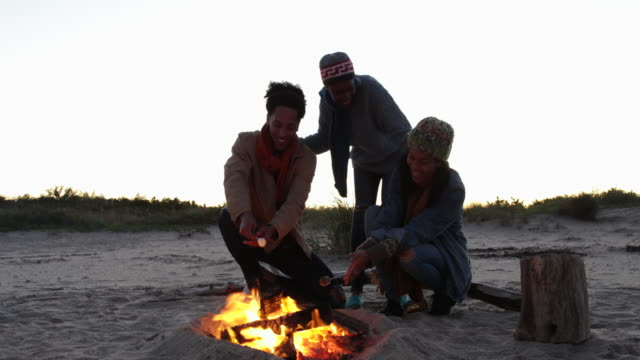 Young woman joins her friends at beach campfire, they are toasting marshmallows.