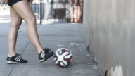 A young woman juggles a soccer ball on a New York Street - closeup - slow motion - 4k