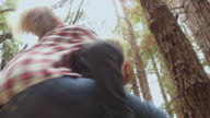 MS TU SLO MO Young woman jumping onto man's back for piggy back ride and spinning / Big Sur, California, USA