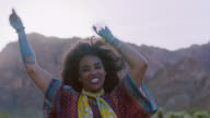 Young woman jumps and dances wild and free in scenic Nevada desert.
