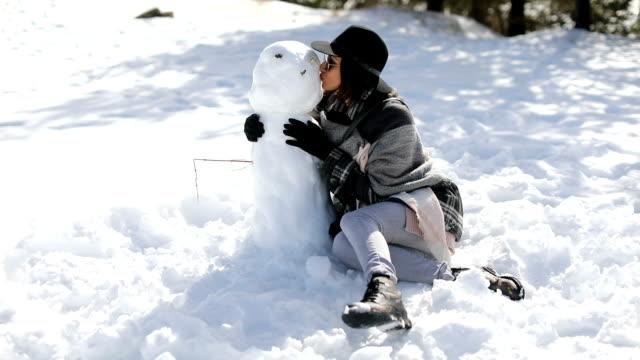 Young woman kissing snowman