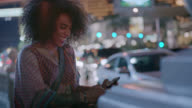 Young woman laughs as she looks at smartphone and looks around for friends on Las Vegas street corner.