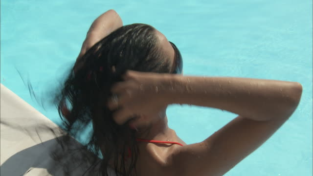 CU HA Young woman leaning on side of swimming pool, Rome, Italy