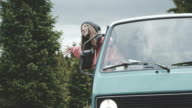 Young woman leaning out of van window and waving.
