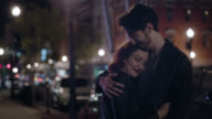 MS SLO MO. Young woman leans on boyfriend and smiles at camera as he puts his arm around her on city street corner.