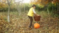 Young woman lifting a pumpkin in the basket.