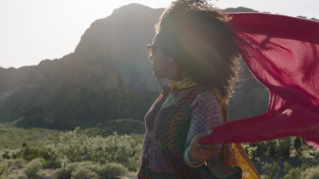 MED SLO MO. Young woman lifts flowing red scarf in the wind and turns to smile at camera in Nevada desert.