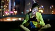 Junge Frau hört Musik am Abend im Freien