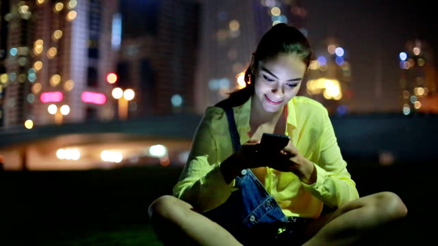 Young woman listening music at night outdoors