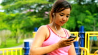 Young woman listening music in playground