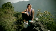 Young woman listing music after fitness exercise in nature