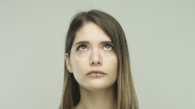 Young woman looking around on gray background