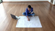 Young woman looking at blueprints and planning