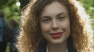 A young woman looking at camera smiling outside in New York City in slow motion