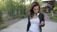 Young woman looking at cell phone, putting on headphones in urban park in Berlin